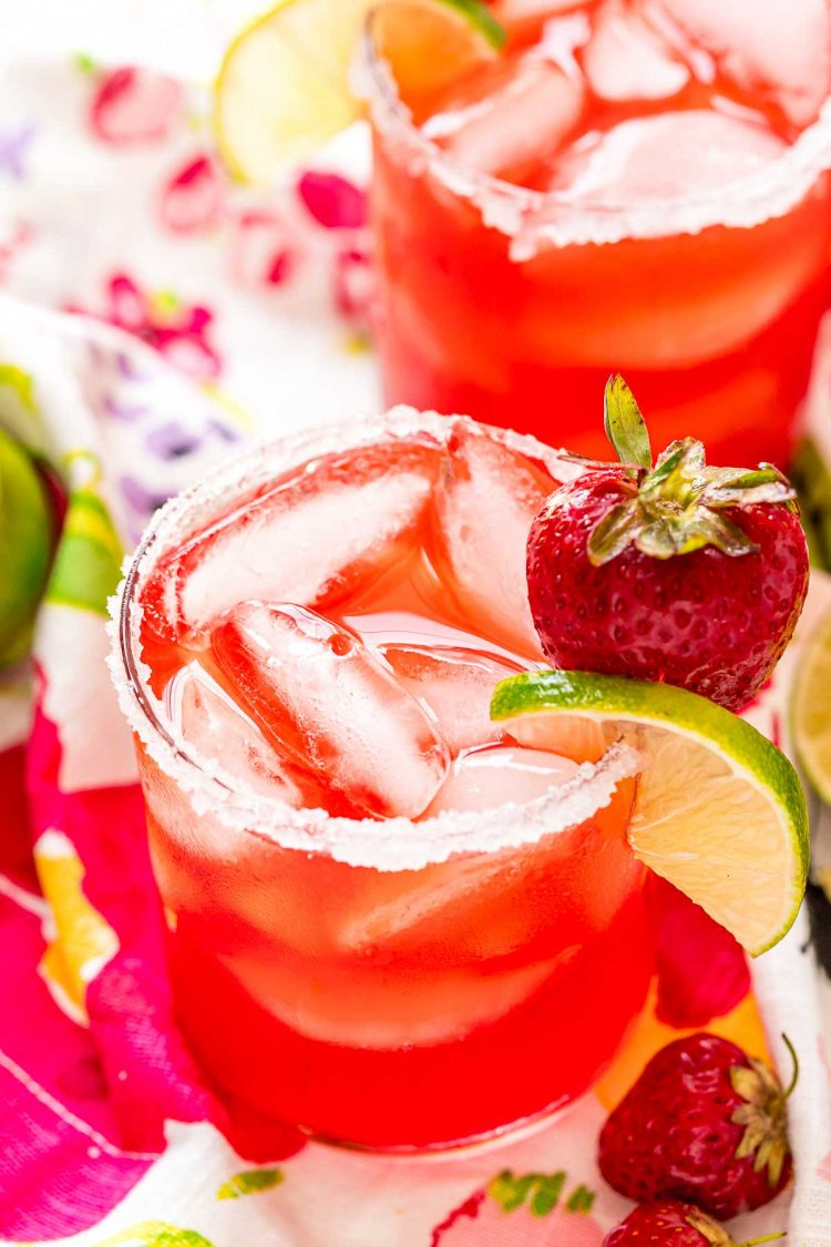 Glass filled with a strawberry cocktail on a colorful napkin with strawberries and limes scattered around it.