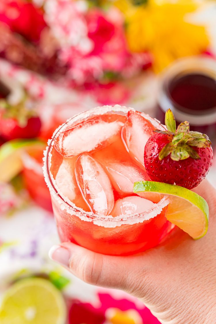 Woman's hand holding a strawberry margarita.