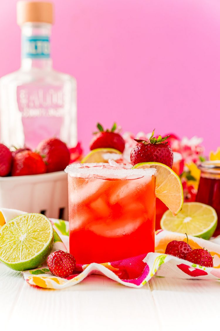 Straight on photo of a strawberry margarita on the rocks garnished with lime wedge and strawberry. Bottle of tequila in the background.