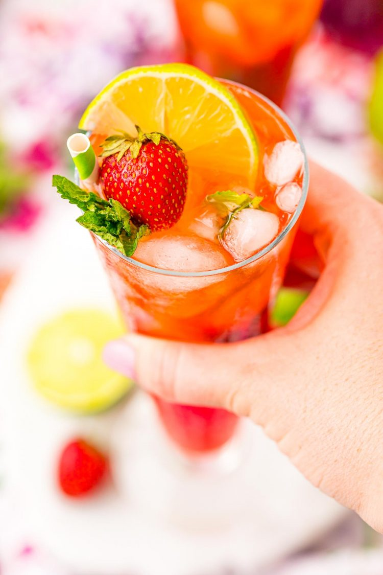 A woman's hand holding a strawberry mojito.