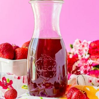 Glass carafe filled with strawberry simple syrup.
