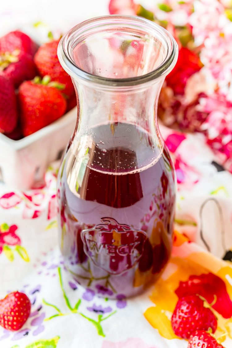 A glass carafe filled with strawberry simple syrup on a colorful napkin.