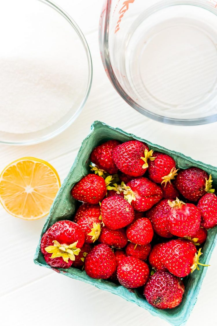 Ingredients to make strawberry simple syrup on a white table.