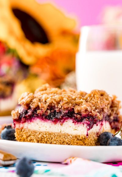 Close up photo of a slice of blueberry cheesecake bars on a white plate with milk and sunflowers in the background.