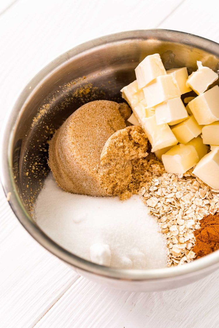 Ingredients to make a crumble topping in a metal mixing bowl.