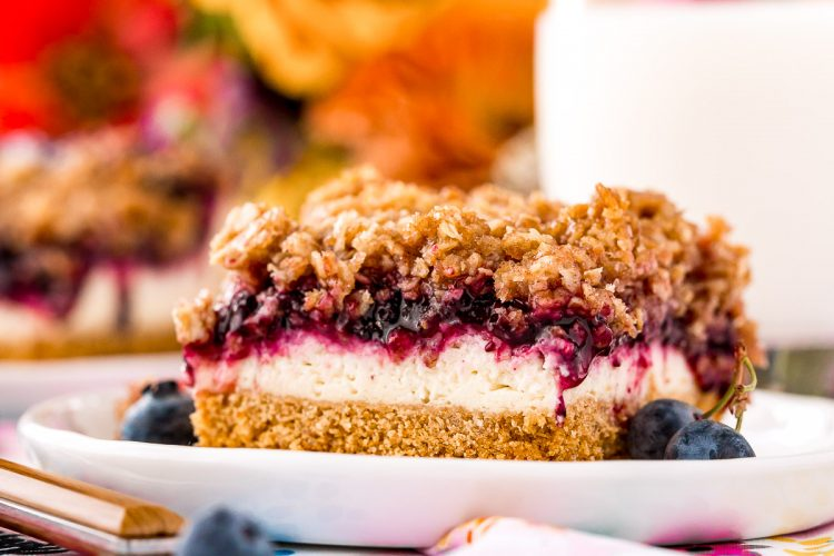 Slice of blueberry cheesecake with crumble topping on a white plate.