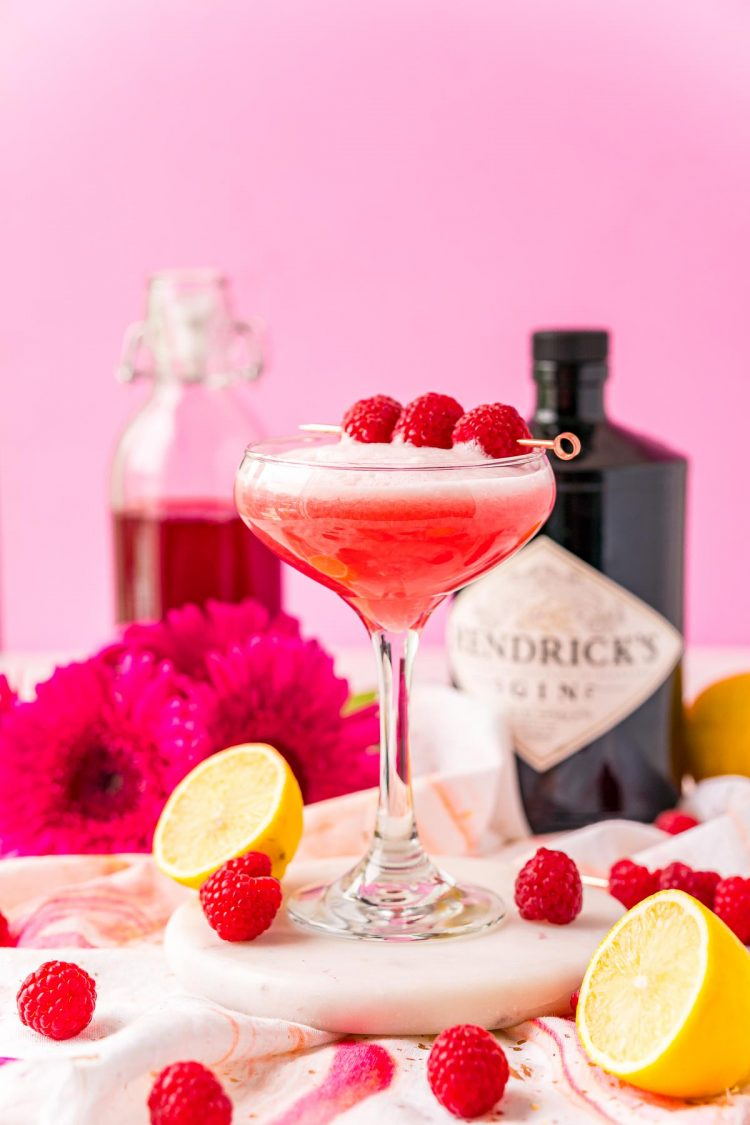 Clover club cocktail surrounded but lemon halves and raspberries with a bottle of gin in the background.
