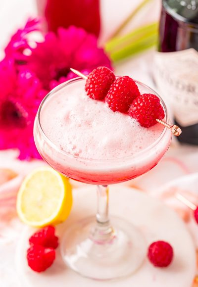 A cocktail glass filled with a pink foamy cocktail garnished with raspberries.