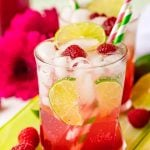 A glass filled with a raspberry lime rickey on a green serving tray with raspberries around it.