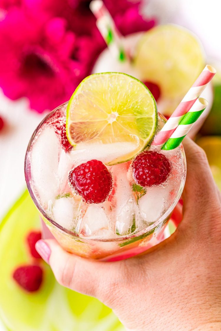 Woman's hand holding a raspberry lime rickey to the camera.