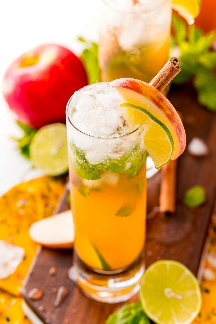 Close up 45 degree angle photo of an apple mojito garnished with lime and apple.
