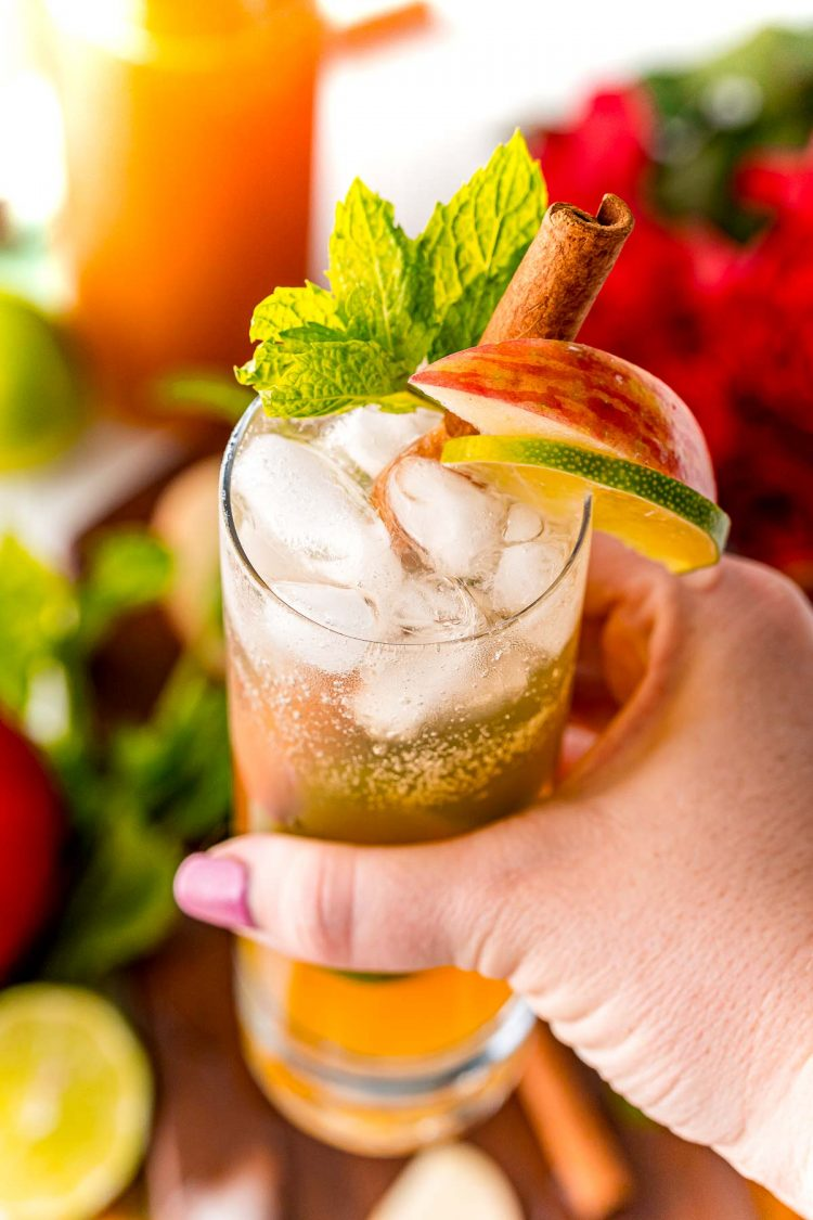 Woman's hand holding an apple mojito up to the camera.