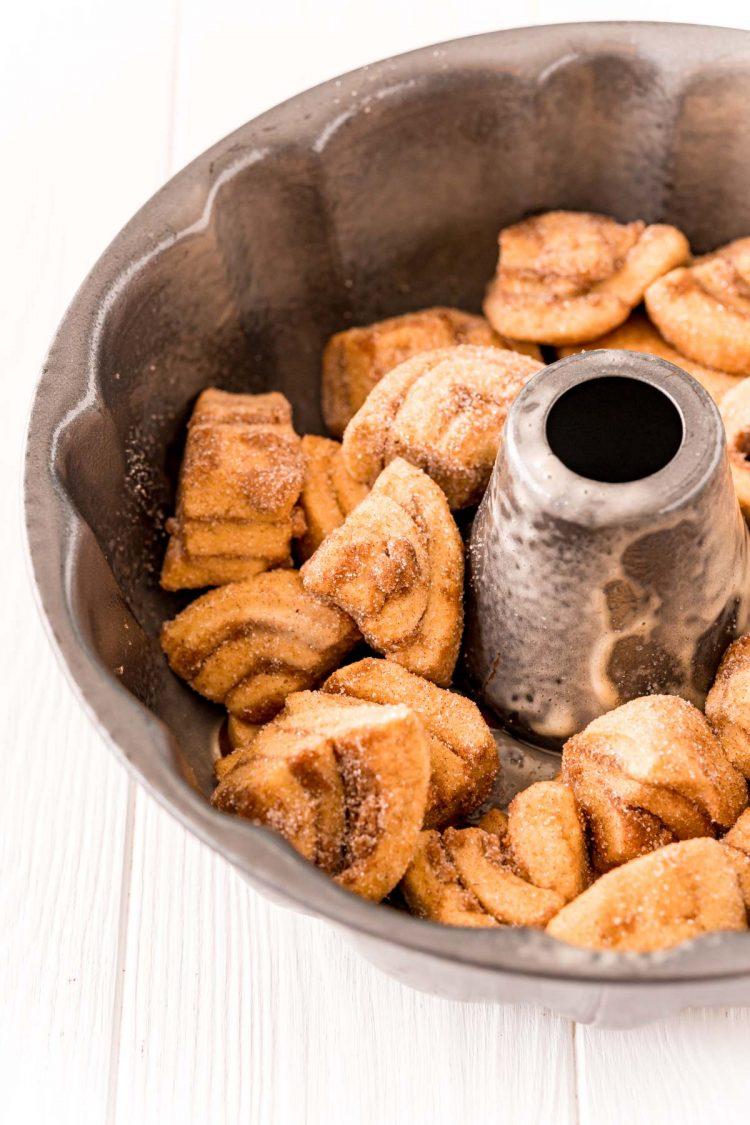 Quartered cinnamon rolls coated in cinnamon sugar in a bundt pan to make monkey bread.