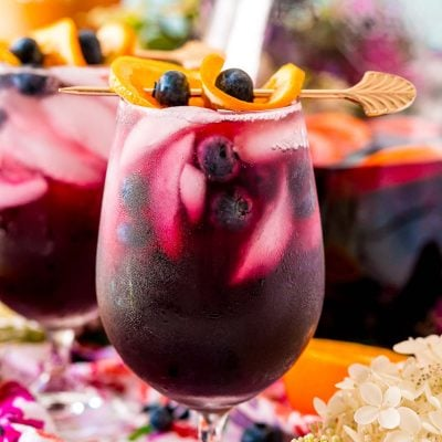 Close up photo of blueberry sangria in wine glasses and in a serving pitcher.