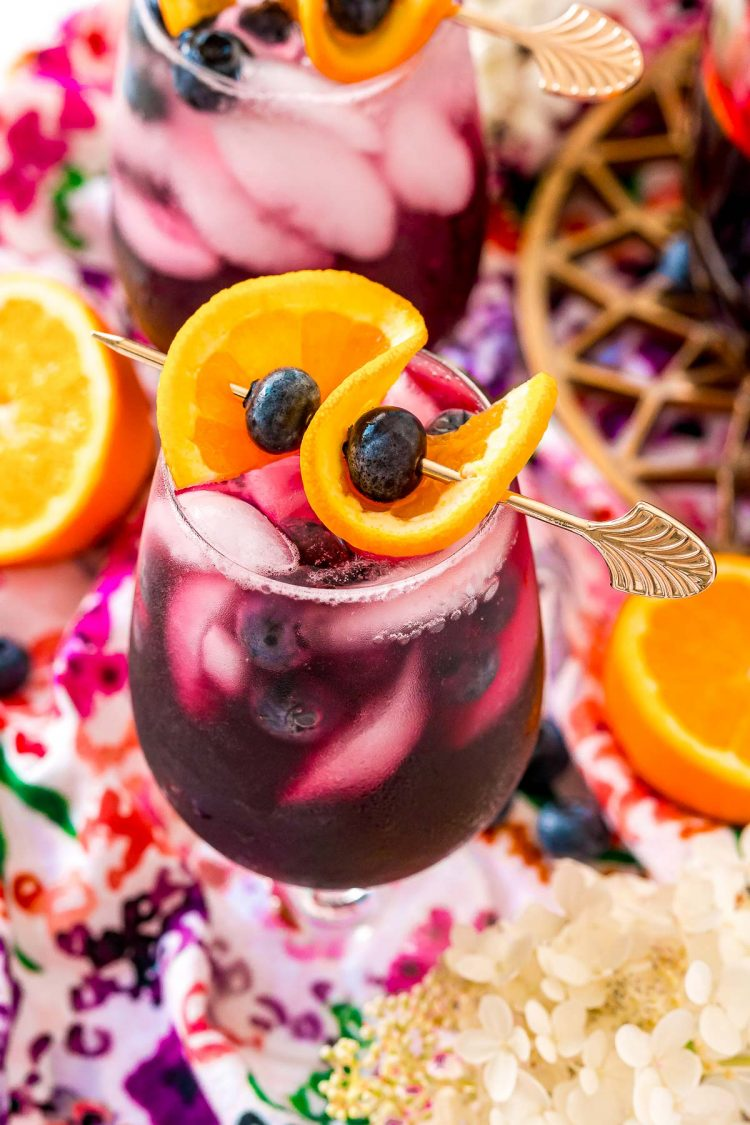 Close up photo of a glass of blueberry sangria topped with a orange slice and blueberries.