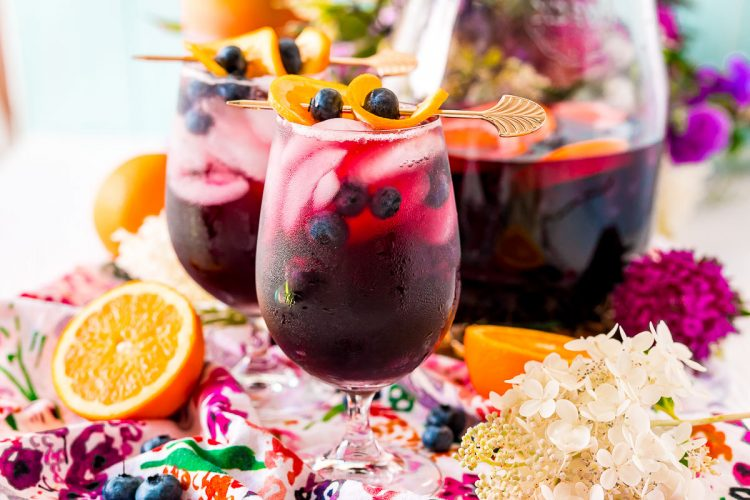 Photo of two wine glasses filled with blueberry sangria on a colorful floral napkin.