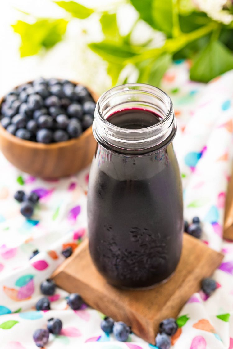 Blueberry simple syrup in a small bottle with blueberries in the background.