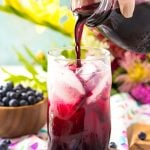 Blueberry simple syrup being poured into a glass of limeade.