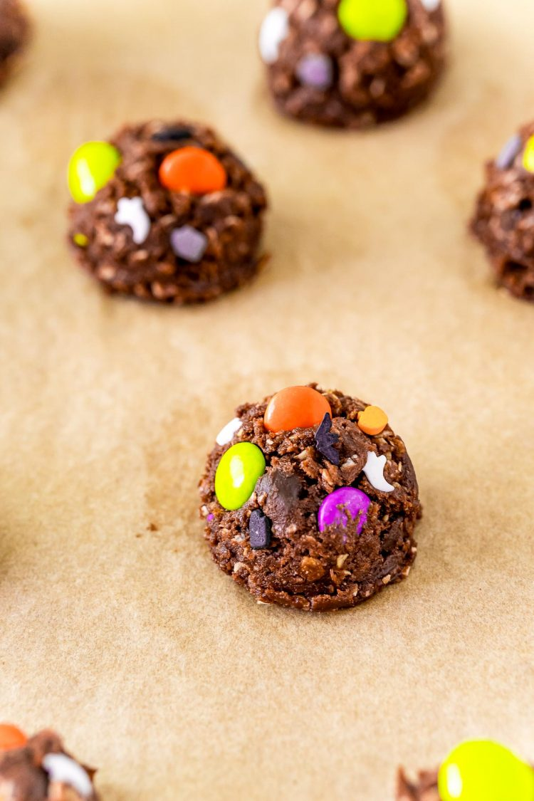 Balls of chocolate cookies dough with halloween sprinkles on parchment paper.