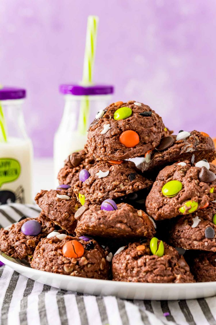 Halloween chocolate cookies on a white plate with a purple background and glasses on milk in the background.