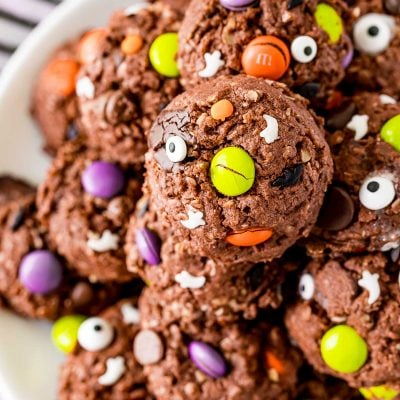 Close up photo of Halloween Monster cookies on a white plate on a black and white striped napkin.