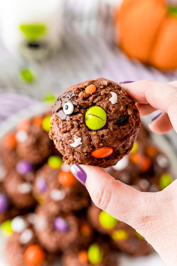 Woman's hand holding a chocolate monster cookie close to the camera.