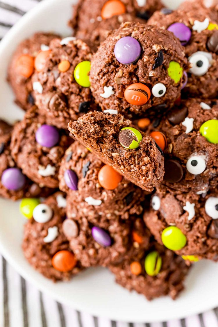 Close up photo of chocolate halloween cookies on a white plate. One of the cookies has a bite taken out of it.