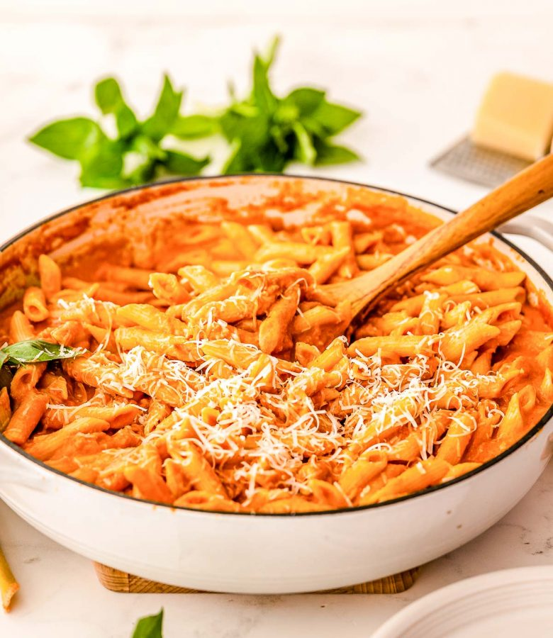 A large skillet filled with penne in vodka sauce with a wooden serving spoon in it.