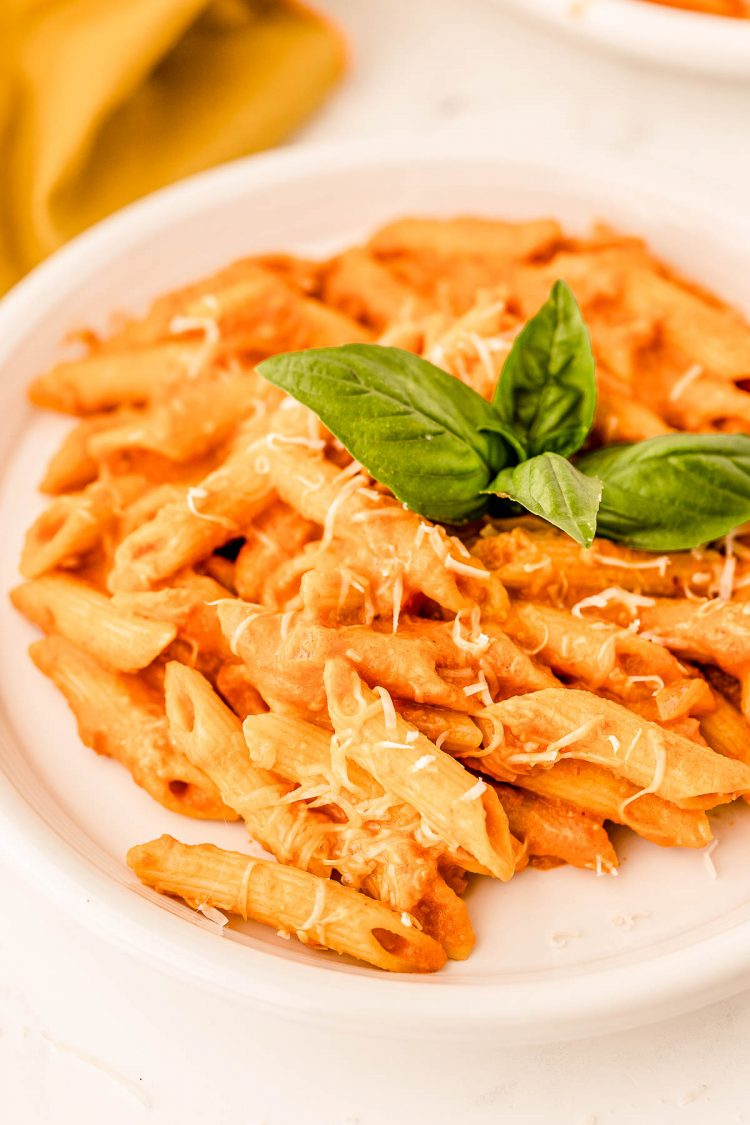 A white plate filled with penne with vodka sauce garnished with a basil leaf.