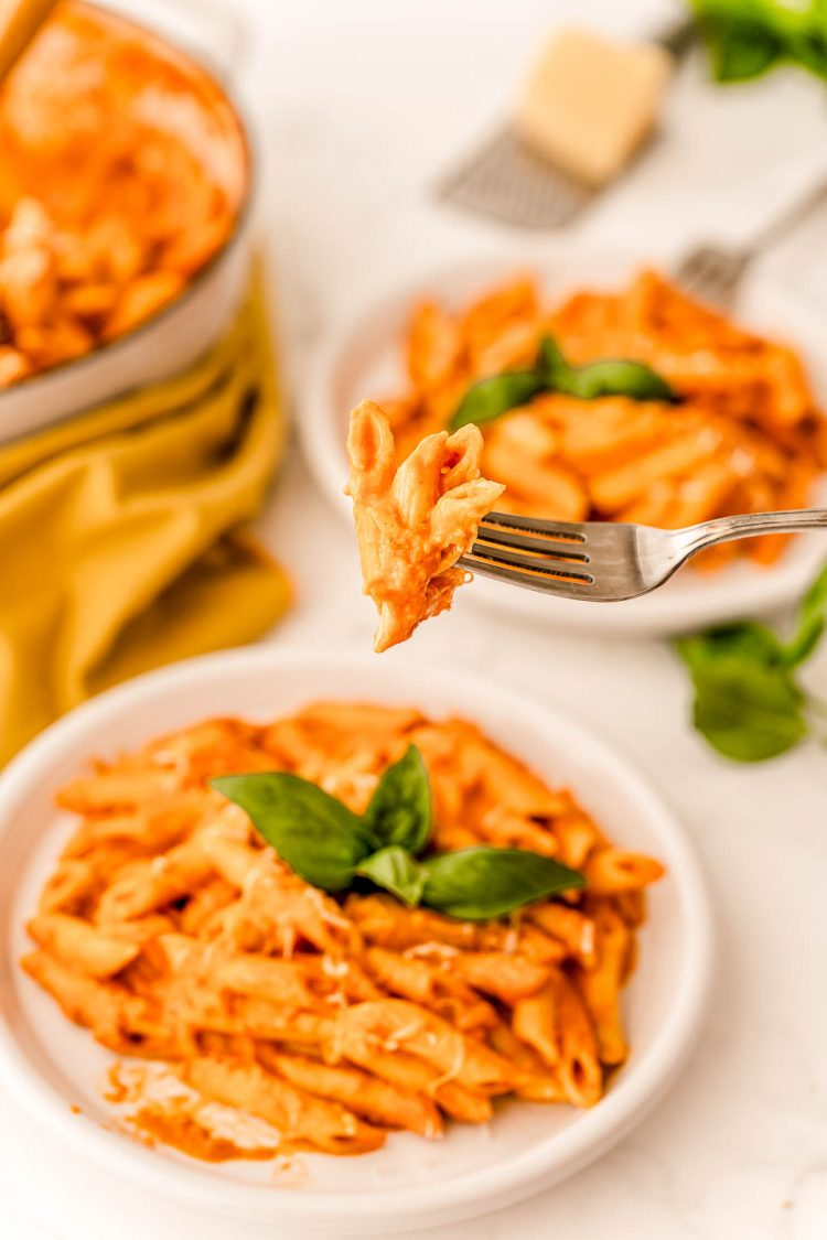 A fork with penne alla vodka being lifted towards the camera.