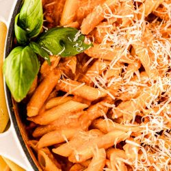 Close up photo of penne in vodka sauce in a skillet.