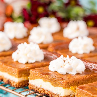 Close up photo of pumpkin pie cheesecake bars on a wire rack.