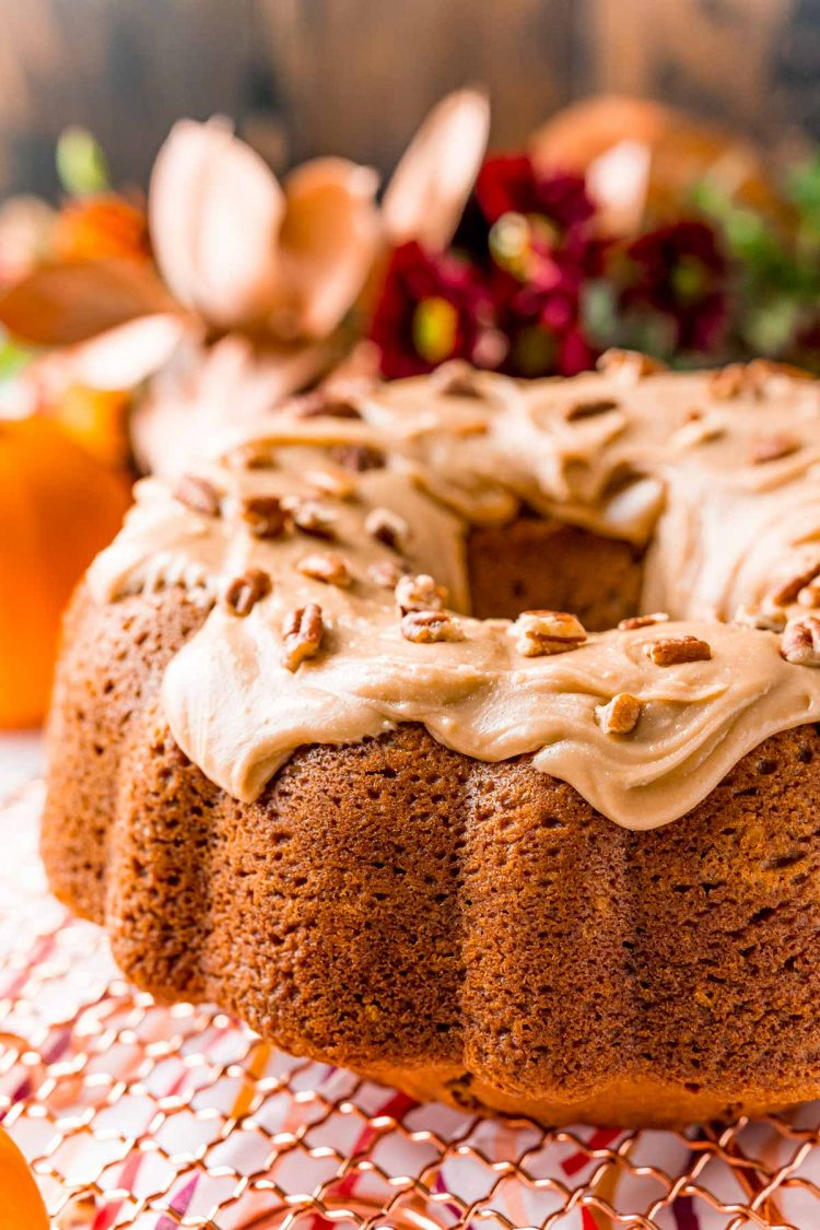 Close up photo of an iced pumpkin bundt cake on a gold wire rack.