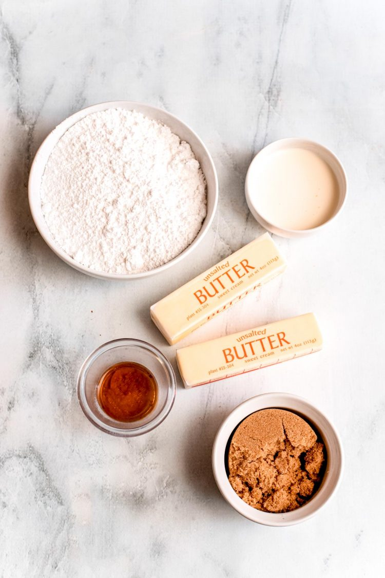Ingredients to make brown sugar frosting on a marble surface.