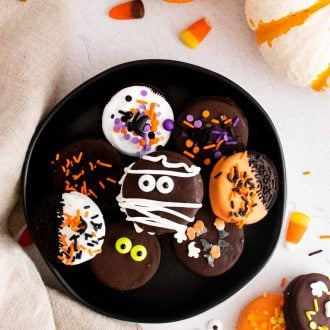 Overhead photo of halloween chocolate covered oreos on a black plate surrounded by pumpkins and candy corn.