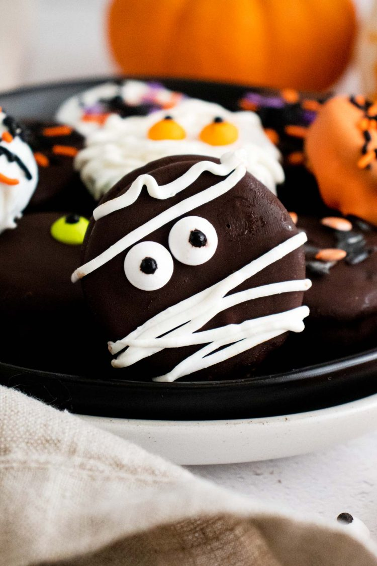 Close up photo of Halloween decorate oreos on a black plate.