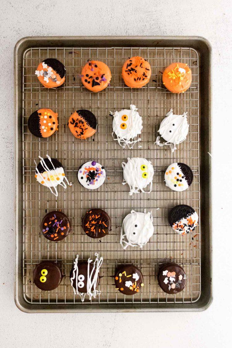Halloween decorated Oreos on a baking sheet.