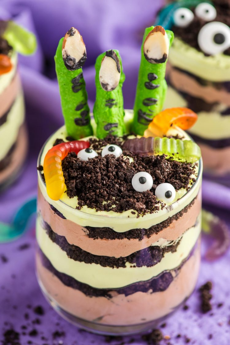 Close up photo of layers Halloween dirt cups with pretzel stick witch fingers, candy eyes, and gummy worms.