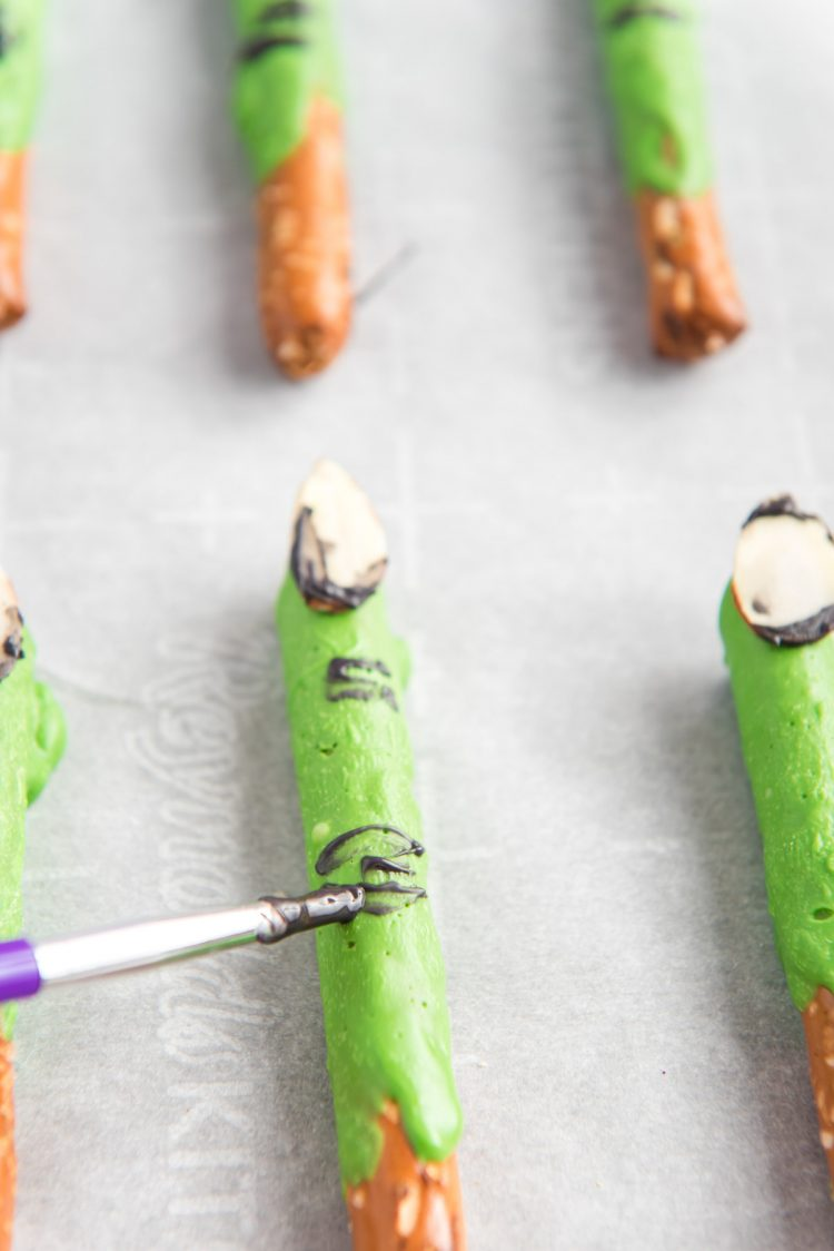 Witch finger pretzel rods being painted.