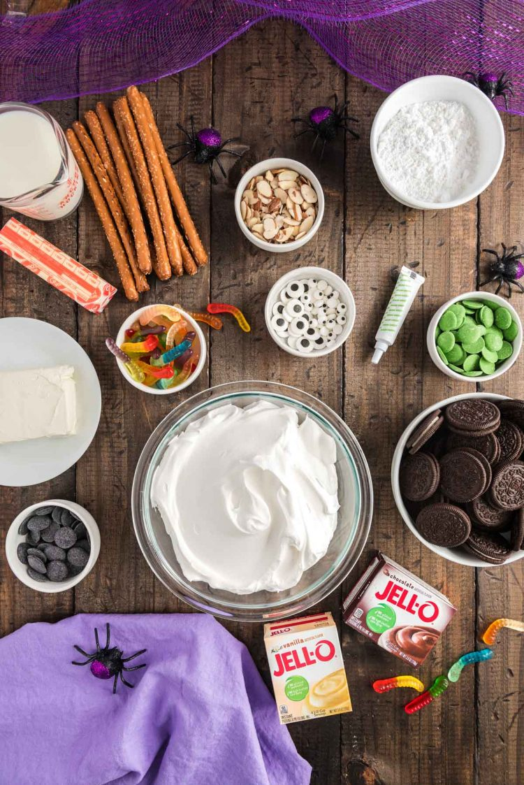 Overhead photo of ingredients to make Halloween themed dirt cups on a wooden table with a purple napkin.