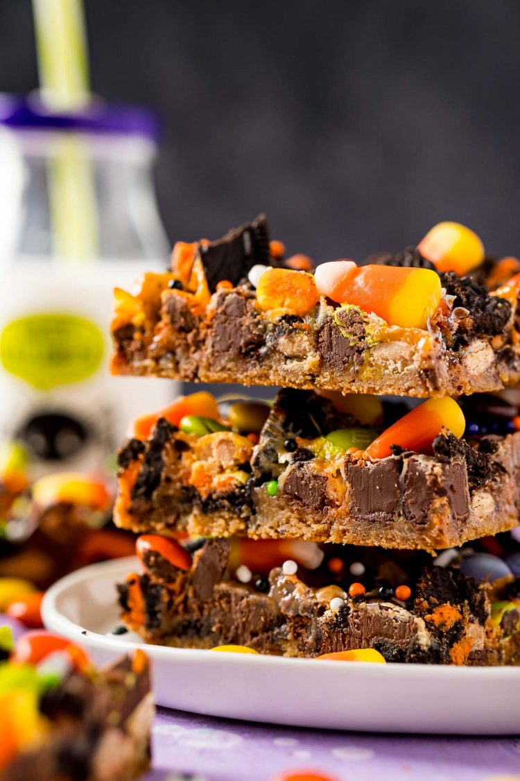 Close up photo of Halloween themed cookie bars on a white plate, stacked three high with a bottle of milk in the background.