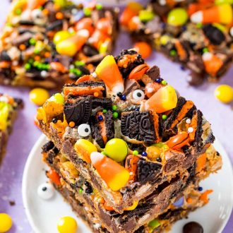 A stack of three halloween magic cookie bars on a small white plate on a purple surface.