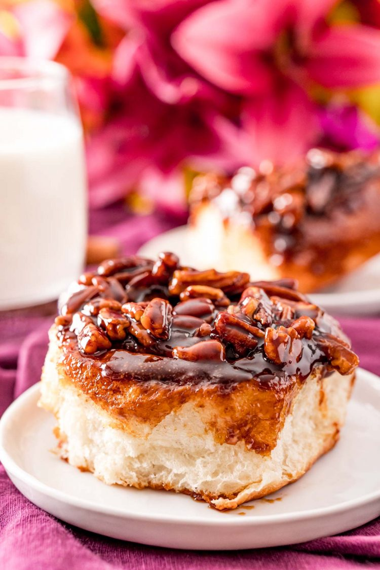 Cinnamon pecan sticky bun on a small white plate with pink flowers and a glass of milk in the background.