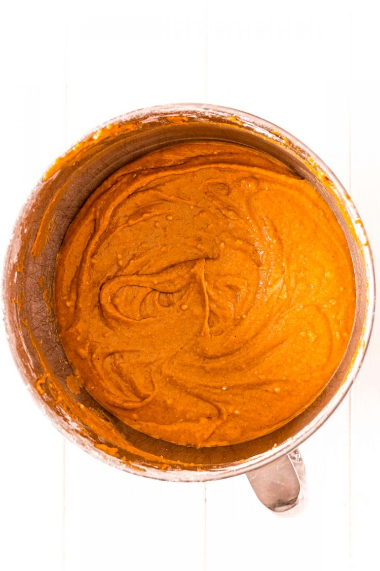 Overhead photo of pumpkin cake batter in a stainless steel mixing bowl.