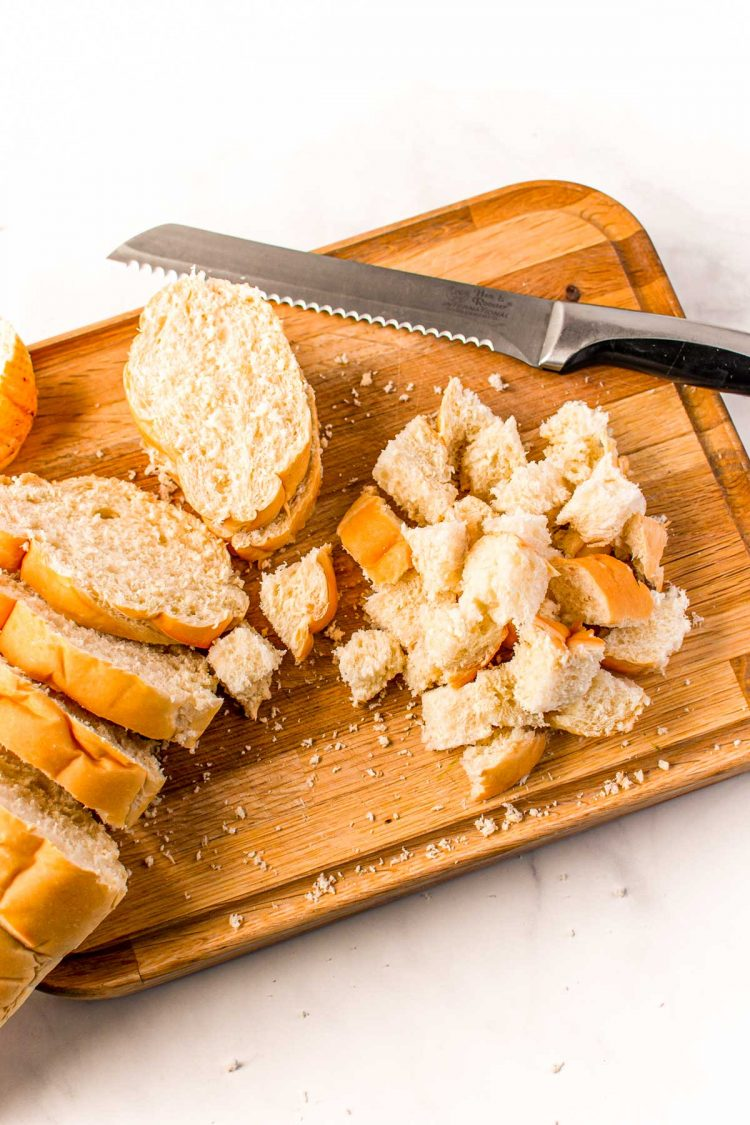 French bread being cut into cubes for stuffing on a wooden cutting board.