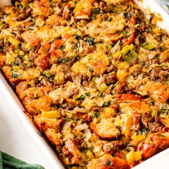 Close up photo of sausage stuffing in a white baking dish with a green napkin next to it.