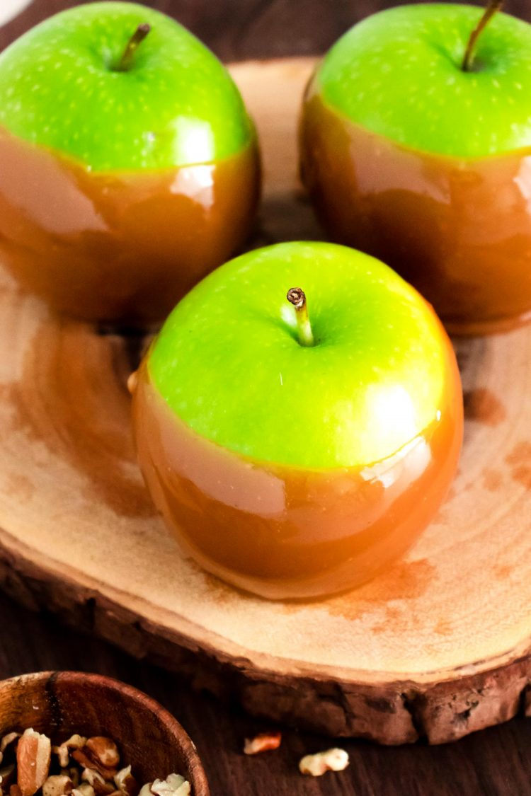 Close up photo of caramel apples on a wooden cake stand.