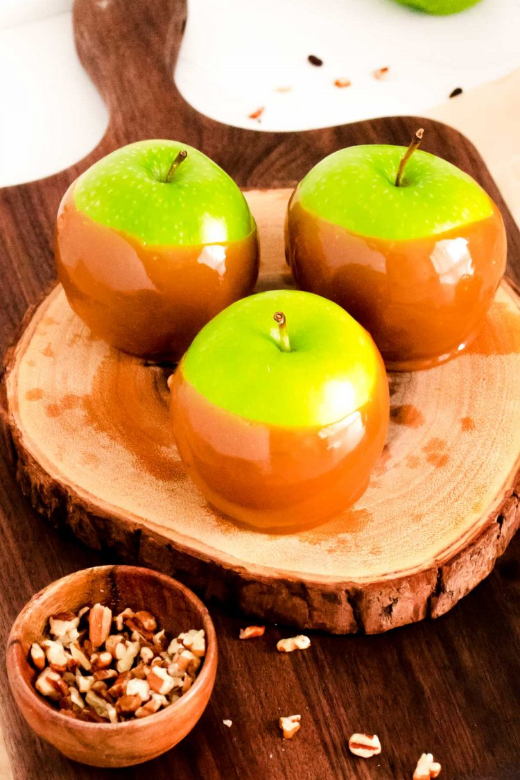 Three caramel dipped apples on a wooden cutting board surrounded by nuts.