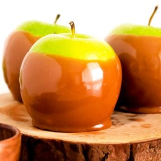 Close up photo of a candied apple on a wooden serving tray.