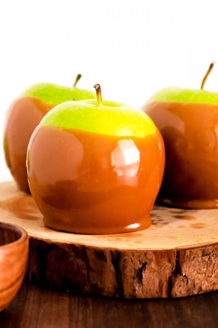 Close up photo of a caramel apple on a wooden serving tray.